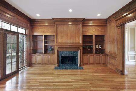 hardwood: Library in luxury home with marble fireplace