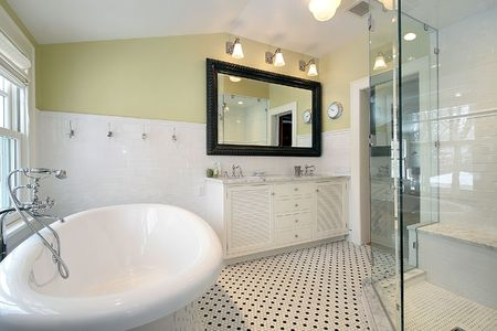Master bath in luxury home with glass shower and large tub photo
