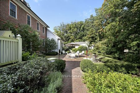 Suburban brick home with patio and bushes photo