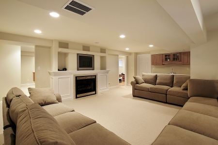 Basement in luxury home with white fireplace photo