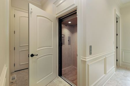home lighting: Elevator in new construction home off of foyer