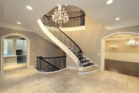 Ontvangsthal met gebogen trap in nieuwbouwhuis Stockfoto