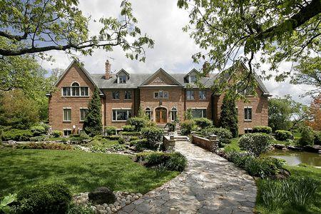 Grote bakstenen huis met stenen loopbrug en landschappelijk