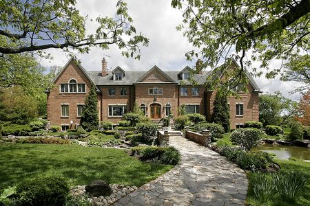 Large brick home with stone walkway and landscaping
