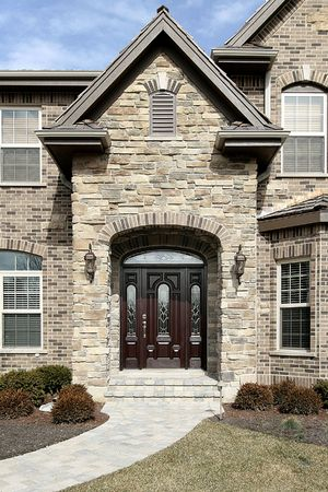 Luxury stone home with stain glass windows on door photo