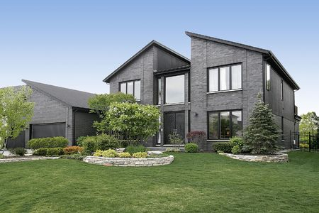 contemporary: Modern home with gray brick and black door