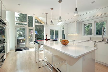 home lighting: Sleek modern white kitchen with eating area Stock Photo