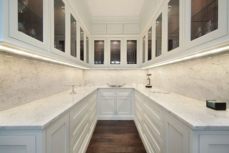 Butlers pantry with white counters and glass cabinets photo