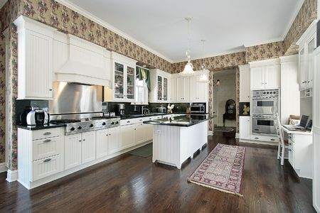 lighting fixtures: Kitchen with white cabinets and desk area