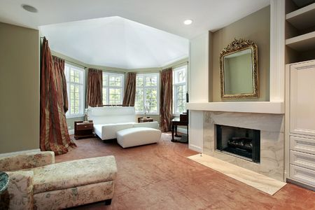 Master slaapkamer in luxe huis met open haard Stockfoto