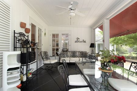 Screened in porch with couch and black floor photo