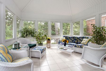 Screened in porch with couch and white tile floor photo