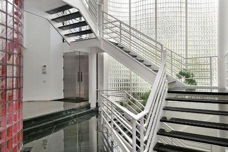 Modern foyer with glass walls and white stairway photo