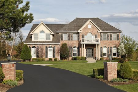 driveways: Luxury brick home in suburbs with pillars Stock Photo