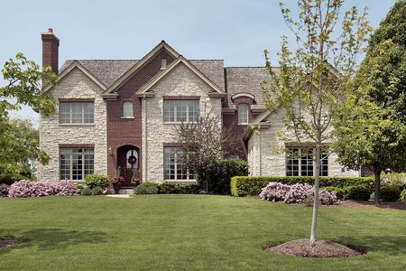 Front view of stone and brick home in spring photo