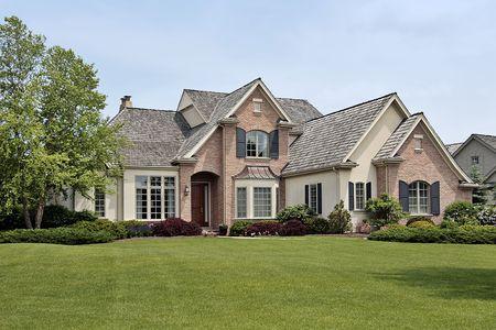 Large luxury brick home in suburban setting