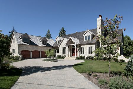 Luxury stone suburban home with three car garage photo