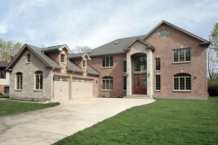 New construction brick home with stone entryway photo