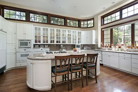 Modern kitchen with white cabinets and multiple windows photo