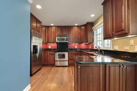 Kitchen with wood cabinetry and red under counter backsplash photo