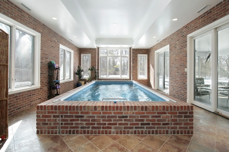 Swimming pool in luxury home inside brick sunroom 版權商用圖片
