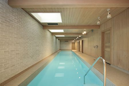 Long indoor swimming pool with wood ceiling beams 版權商用圖片