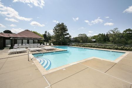 pool deck: Swimming pool in housing development with deck chairs Stock Photo