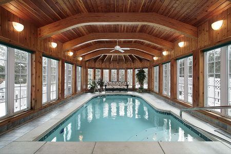Swimming pool in luxury home with wood ceiling beams