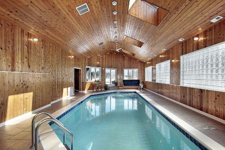 Swimming pool in luxury home with wood paneled ceiling