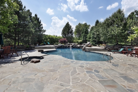 Swimming pool of luxury home with large stone patio photo