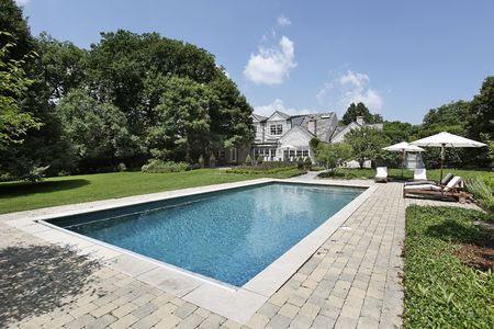pool deck: Swimming pool of luxury home with deck chairs