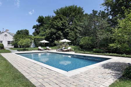 swimming pool home: Swimming pool of luxury home with deck chairs