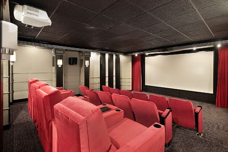 Home theater in luxury home with red chairs photo