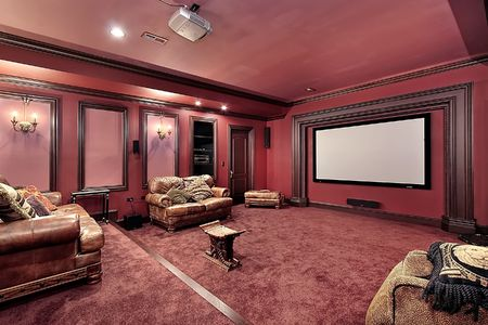 Large theater in luxury home with maroon walls photo