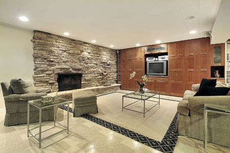 Lower level family room with stone fireplace Stock Photo