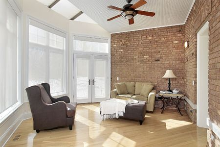 living room sofa: Sun room with windows and brick wall Stock Photo