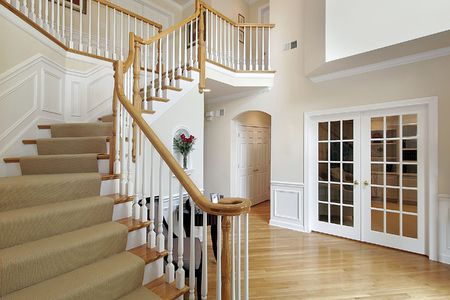 Foyer in luxury home with wood staircase photo
