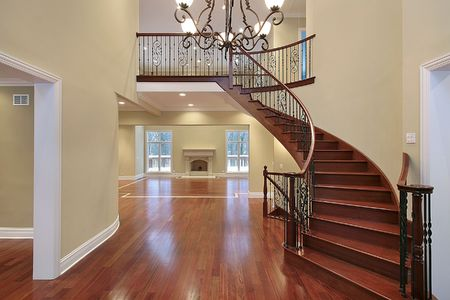 Cherry wood foyer with balcony and curved staircase photo