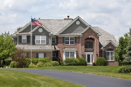 custom home: Luxury brick home in suburbs with American flag Stock Photo