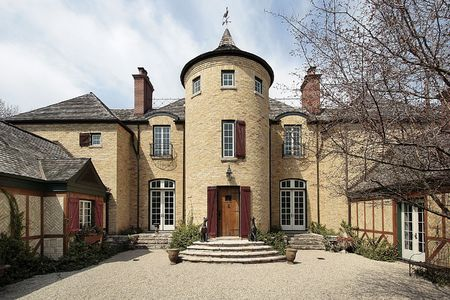 turret: Courtyard of large home with stone turret Stock Photo