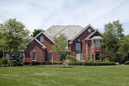 Large brick home in suburbs with cedar roof photo
