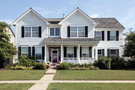 front porch: Blanco hogar en los suburbios con porche frontal