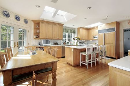 Kitchen with wood cabinets and white island photo