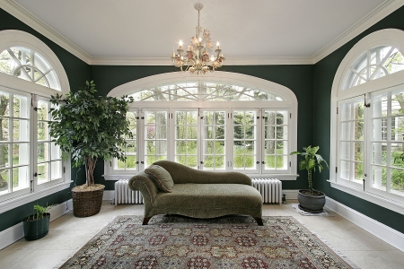 Sunroom in luxury home with sofa and wall of windows