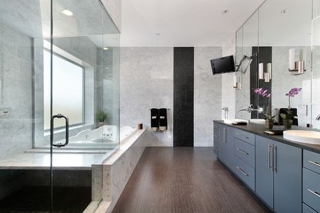 Sleek master bath in luxury home with glass shower photo