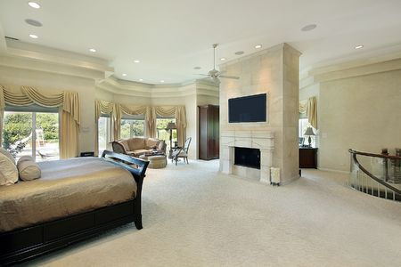 luxury bedroom: Master bedroom in luxury home with fireplace Stock Photo