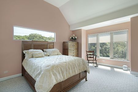couches: Master bedroom in suburban home with mauve colored walls