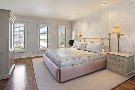 Master bedroom in suburban home with wood floors photo