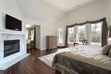 Master bedroom in new construction home with marble fireplace