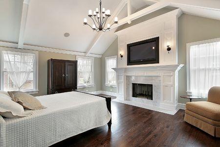 Hoofd slaap kamer in luxe huis met marmeren open haard Stockfoto